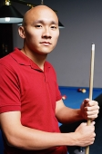 Man holding pool cue, looking at camera - Asia Images Group