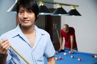 Man holding pool cue, smiling at camera - Asia Images Group