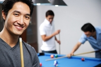 Man holding pool cue, smiling at camera, people in the background - Asia Images Group