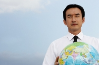 Businessman holding globe, looking away - Asia Images Group