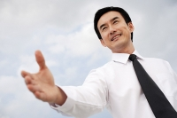Businessman with hand outstretched, low angle view - Asia Images Group