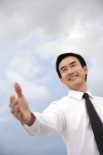Businessman with hand outstretched, smiling - Asia Images Group