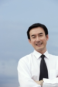 Businessman with arms crossed, smiling at camera - Asia Images Group