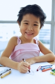 Young girl with crayons, smiling at camera - Asia Images Group