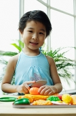 Young girl playing with plastic food, smiling at camera - Asia Images Group