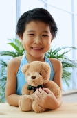 Young girl holding teddy bear, smiling at camera - Asia Images Group