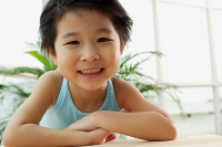 Young girl smiling at camera, leaning on table - Asia Images Group