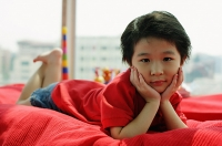 Young girl lying on sofa, looking at camera, hands on face - Asia Images Group