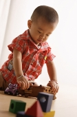 Young boy playing with toy train - Asia Images Group