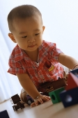Young boy on floor, playing with toy train - Asia Images Group