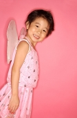 Young girl in pink dress with wings attached, looking at camera, side view - Asia Images Group