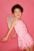 Young girl in pink dress with artificial wings, smiling at camera, hands stretched behind her - Asia Images Group
