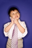 Boy wearing oversized tie, using mobile phone - Asia Images Group