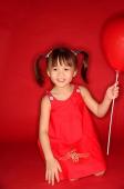 Girl holding heart shaped balloon, kneeling on floor - Asia Images Group