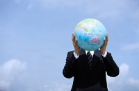 Businessman holding globe, covering his face - Asia Images Group