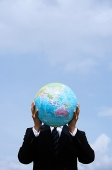 Businessman holding globe in front of his face - Asia Images Group