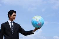 Businessman holding globe, arms outstretched - Asia Images Group