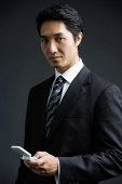 Businessman, looking at camera, holding mobile phone - Asia Images Group