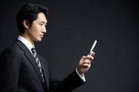Businessman holding mobile phone - Asia Images Group