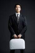 Businessman standing, carrying briefcase - Asia Images Group