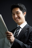 Businessman holding newspaper, smiling - Asia Images Group