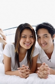 Couple on bed, smiling at camera - Asia Images Group