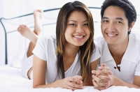 Couple side by side on bed, smiling at camera - Asia Images Group