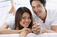 Couple side by side on bed, smiling - Asia Images Group