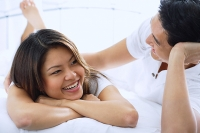 Couple on bed, smiling - Asia Images Group