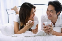 Couple on bed, holding mugs, smiling at each other - Asia Images Group