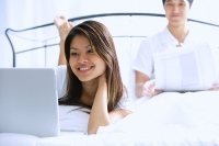 Couple on bed, woman using laptop, man behind her, reading newspaper - Asia Images Group