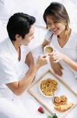 Couple on bed, having breakfast - Asia Images Group