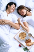 Couple lying on bed, breakfast on tray next to them - Asia Images Group