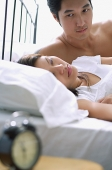 Couple lying on bed, woman sleeping, man watching her - Asia Images Group