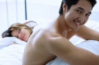 Man sitting on bed, smiling at camera, woman asleep next to him - Asia Images Group