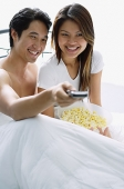 Couple sitting on bed, smiling, watching TV - Asia Images Group