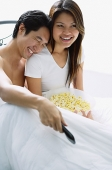 Couple sitting on bed, smiling, watching TV, man leaning on womans shoulder - Asia Images Group