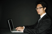 Businessman wearing glasses, with laptop, portrait - Asia Images Group
