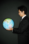Businessman looking at globe in hands - Asia Images Group