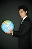 Businessman holding globe in hands, looking at camera - Asia Images Group