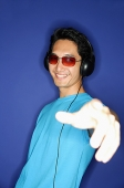 Man wearing sunglasses, wearing headphones, hand outstretched - Asia Images Group