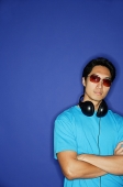 Man with sunglasses, headphones around his neck, arms crossed - Asia Images Group