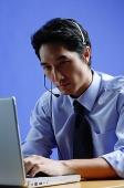 Man wearing headset, using laptop - Asia Images Group