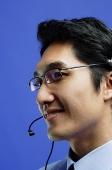Man wearing headset, looking away, smiling - Asia Images Group