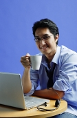 Man sitting in front of laptop, holding mug, smiling at camera - Asia Images Group