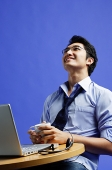 Man sitting in front of laptop, holding mug, looking up - Asia Images Group