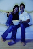Couple sitting on sofa, watching TV, bowl of popcorn between them - Asia Images Group