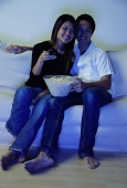 Couple sitting on sofa, watching TV, woman holding remote control - Asia Images Group