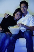 Couple sitting on sofa, watching TV, portrait - Asia Images Group