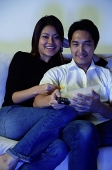 Couple watching TV, eating popcorn - Asia Images Group